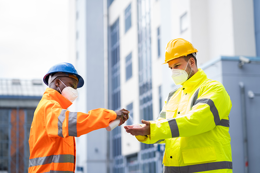 Construction Workers Using Hand Sanitizer